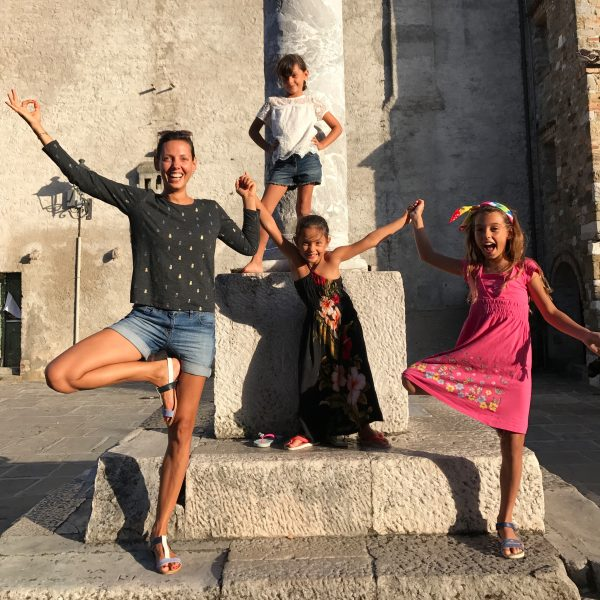 dani and her three girls in a yoga pose in Itlay on a piazza
